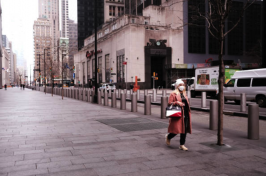 A single woman walks down an empty New York City street in a mask