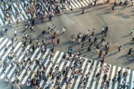 A large amount of people walk across cross walks