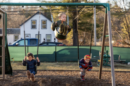 Children swing on swings outside of their early learning center in New Hampshire