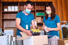Two nonprofit workers backing supplies in boxes