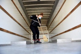 Woman sweeps out a moving van