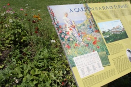 Sign with text in front of bright garden flowers