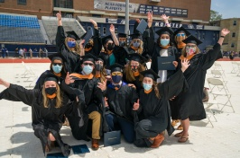 graduate students in caps and gowns after receiving diplomas