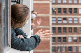 Image of women waving outside their windows with masks