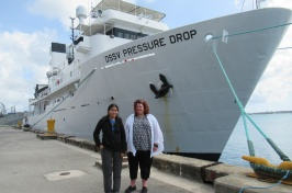 Jaya Roperez and Rochelle Wigley stand on a dock in front of the DSSV Pressure Drop vessel.