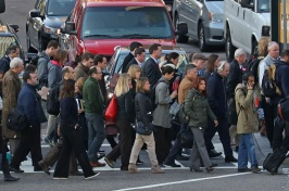 A large group of people cross a busy city street.