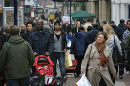 People of different races and ethnicities walk together on a crowded sidewalk.
