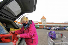 An elderly woman loads groceries into her trunk