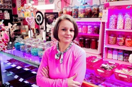 A small business owner stands in her candy shop with colorful jars and items on display behind her.