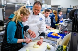 Chef Ron and a young female student work together to cut an onion