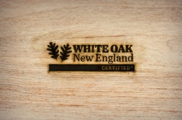 "Logo with leaves and words ""White Oak New England Certified"" are branded on piece of wood"