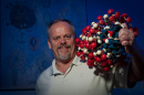Professor Kelley Thomas holding a large molecule model