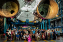large group of scientists and students pose beneath a rocket ship