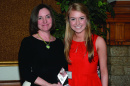 Christine Carberry '82 and Megan Cooley '17 pose for a photo with an award.