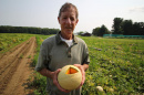 UNH professor emeritus of plant biology and genetics J. Brent Loy holding a cantaloupe in a field