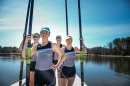 UNH rowers on a dock holding oars