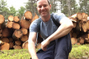 Greg Jordan in front of a log pile