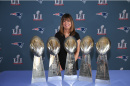 Louise Griffin standing in front of Patriots 5 Super Bowl trophies