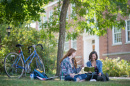 Two women sitting under a tree on a summer day at UNH