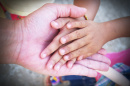 Image of grandparents' hand holding a child's hand