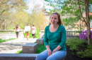 UNH's Allison Lehoux '18 sitting on a bench outside of James Hall at UNH