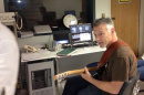 Professor Don Robin playing the guitar while subject undergoes brain scan.