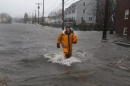 A rescue worker walked through flooded Sea Street during the first nor'easter of March. (JOHN TLUMACKI/GLOBE STAFF)