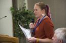 Postdoctoral researcher Kerri Seger speaks into a microphone