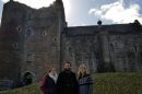 Two UNH students and a UNH alumna in front of a castle in Scotland