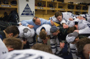 Coach Dick Umile and UNH hockey players in the locker room before a game