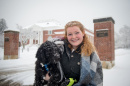 UNH student holding dog on sidewalk in front of Hamilton Smith Hall during snow storm