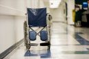 photo of wheelchair in empty hospital hallway