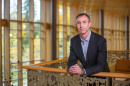 Assistant Professor of Organizational Behavior Michael Kukenberger posing next to railing
