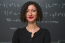 Chanda Prescod-Weinstein stands in front of a chalkboard with equations