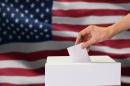 A hand putting a ballot into a ballot box