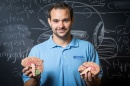 Neuropsychology professor Daniel Seichepine holds models of the brain