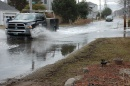 Two vehicles drive through flooded road conditions.