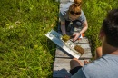 Researchers bent over soil sample on small boardwalk over a fen