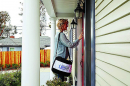 A woman working for the U.S. Census Bureau knocks on the door of someones home