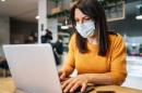 A women wearing a mask sits at a laptop