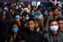 Masked people walk on a busy street