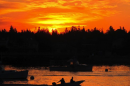 A lobsterman and his crew member head out to his fishing boat as the sun rises over Bass Harbor on Mount Desert Island.