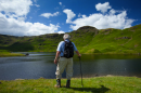 Man stands at the edge of a lake looking at the green rolling hills