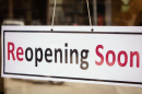"""Picture of a sign hanging on a door that says """"reopening soon"""""""