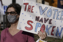"A woman in a mask and glasses hold a sign that says ""the voters have spoken"""