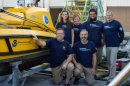 The Autonomous Surface Vehicle team stands next to a yellow vessel.