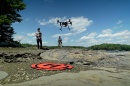 Two people fly a drone on a rocky coast