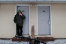A man stands in the doorway of his apartment smoking a cigarette