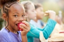 Image of girl eating apple accompanied by other kids