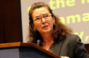 """Dr. Schuh standing at podium in the Dirksen Senate Office Building, with a serious expression on her face, as she addresses the members of AUCD about the importance of the Access to Free Speech for All Act"""">"""